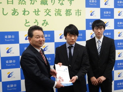 報告書提出の様子(左より花岡市長、松原さん、高森さん)