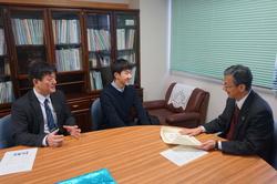 土居校長(右)に入賞を報告する久保田さん(中央)と指導教員の柄澤教授(左)