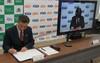 協定書に署名する土居校長(左)、KDDI株式会社 松野 茂樹 理事(右)